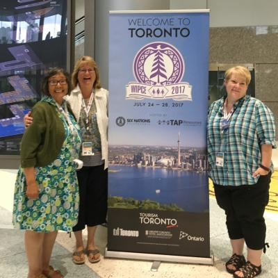"Annie Conger, Doreen Hayward and Lynda McGilvary standing next to a ""Welcome to Toronto"" sign at the 2017 World Indigenous Peoples Conference on Education"